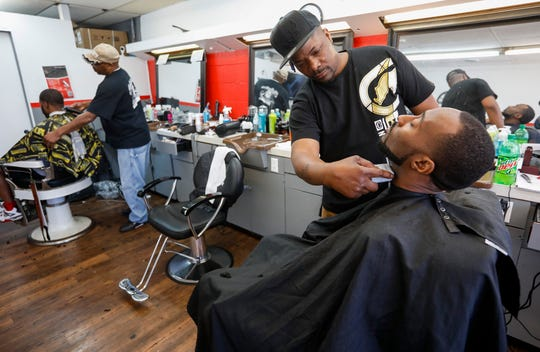 Donald Spencer, the owner of Reflections Barber Shop, gives George Mathis a haircut and beard trim on March 25, the day before Springfield's stay-at-home order took effect. Barbershops and hair salons are considered nonessential businesses and will be closed during the 30-day order.