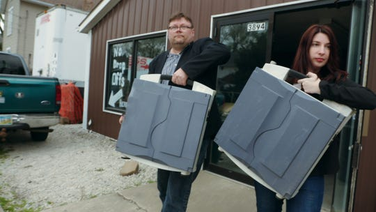 From left: Harri Hursti and Maggie MacAlpine carry voting machines they purchased.