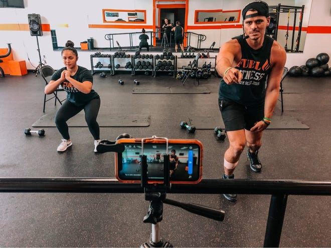 A pair of instructors at Fuel Fitness lead a virtual boot camp workout streamed live on Facebook.