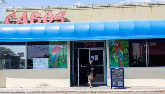 A customer walks out of Cabo's Island Bar and Grill with a takeout order, Wednesday, March 25, 2020.