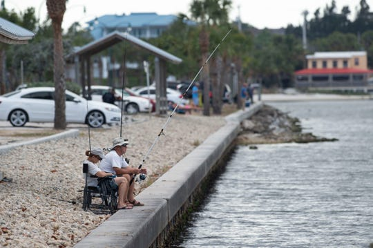 People fish and relax along the Indian River Lagoon on Wednesday, March 25, 2020, at the Jensen Beach Causeway. Most fishing spots remain accessible as the coronavirus pandemic spreads, except for public beaches and the facilities at popular parks Sebastian Inlet State Park and Fort Pierce Inlet State Park. Locals hope many fishing piers will remain open.