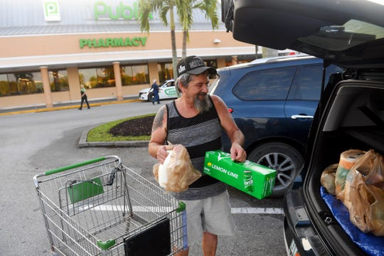 Tim Nerat, of Vero Beach,  places his groceries in the trunk of his car on Wednesday, March 25, 2020, after taking advantage of an early hour of shopping at the Publix Super Market on 58th Avenue in Indian River County. The grocery store chain is opening an hour early on Tuesdays and Wednesdays to allow customers 65 and older to purchase food and paper products.