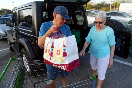 "Vicki and Jim Herman, of Vero Beach, unload their shopping cart on Wednesday, March 25, 2020, after taking advantage of the extra hour of shopping at the Publix Super Market on 58th Avenue in Indian River County. The grocery story chain is opening their doors an hour early on Tuesdays and Wednesdays from 7 a.m. to 8 a.m. to allow customers 65 and older to shop for needed groceries and paper products. ""They were doing a really good job helping people, and we told them so,"" said Vicki Herman."