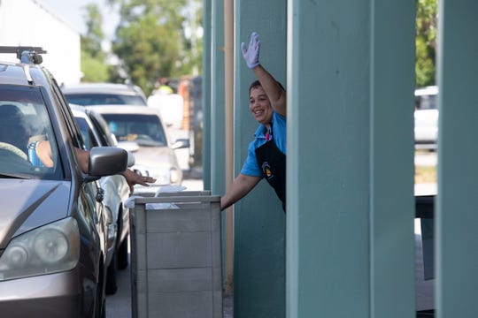 Murray Middle School cashier Wanda Felipe waves to students as she helped distribute meals to families staying in their vehicles as the district transitions to distance learning because of the coronavirus pandemic Wednesday, March 25, 2020, at Port Salerno Elementary School. The district Tuesday announced it would cancel summer camps and offer summer programs virtually.