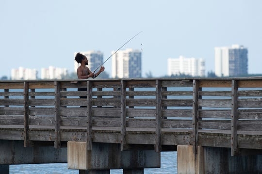 Angel Villegas, of Port St. Lucie, fishes the Indian River Lagoon on Wednesday, March 25, 2020, at the Jensen Beach Causeway. Most fishing spots remain accessible as the coronavirus pandemic spreads, except for public beaches and the facilities at popular parks Sebastian Inlet State Park and Fort Pierce Inlet State Park. Locals hope many fishing piers will remain open.