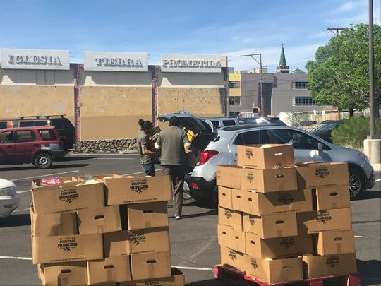 Volunteers at the Kelly Center for Hunger Relief distribute a box of food to a client Tuesday morning