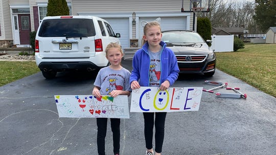 Sophia and Ava Melnick of Vineland wait curbside to greet Mennies Elementary School therapy dog, Cole, who visited their neighborhood during a recent road trip.