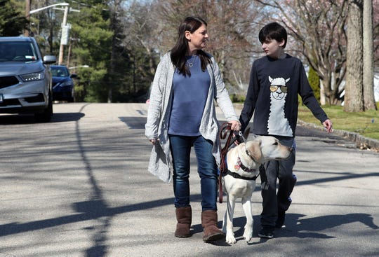 Sandy Millman and her son Alex walk with Alex's service dog Clancy in their Scarsdale neighborhood March 24, 2020. Service dogs are helping families with kids who have autism now that there is a change in routine due to the coronavirus, and people are staying at home.