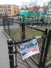 A Playgrounds and Courts Temporarily Closed sign hangs on the fence at Francis Heafy Park on Van Cortlandt Park Avenue in Yonkers, March 25, 2020.