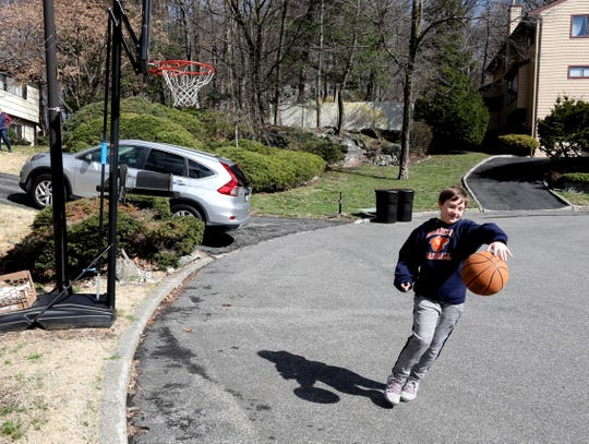 Joe Mulligan, 9, plays basketball outside their home in Briarcliff Manor, N.Y. March 24, 2020. In October of 2019, Joe was diagnosed with EHE, a rare form of cancer. Other than regular scans to track the disease, there is no treatment for the cancer. During the coronavirus pandemic, Joe's parents, Jennifer and Jim, are afraid that he may not be able to get his regular scans as medical care may be diverted to those diagnosed with the virus.