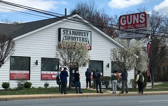 People line up outside StarQuest Shooters and Survival Supply on Concord Pike Tuesday. The store said in a Facebook message later that day that the store, which sells a variety of survival gear and food besides guns, was ordered closed by state authorities.