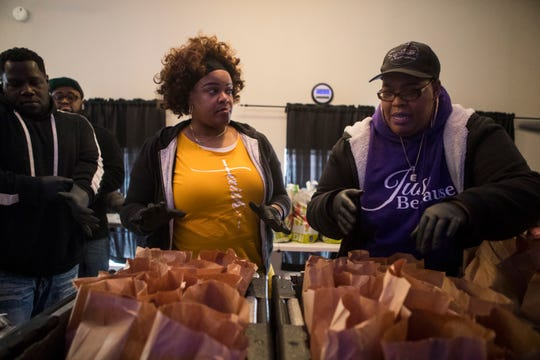 Volunteers with the #TheGiveBack group hand out free lunches and food packages to residents in need Wednesday afternoon at IHUB Church in Hedgeville. Co-organizer Angell Morris has been giving our food at various spots around Wilmington since the state was hit hard with the coronavirus outbreak last week.