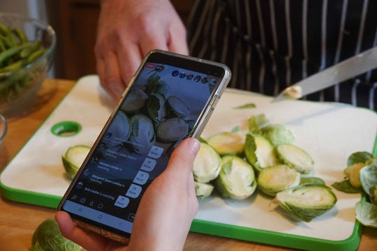 13-year-old Ellie records a tight shot of he father, chef Robert Lhulier, as he demonstrates how to cut brussel sprouts during a Facebook Live in their home kitchen.