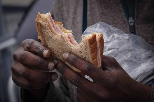 A homeless man eats a sandwich made by cafe workers at the state Division of Public Health, that was distributed to people in need in the Dover area on Tuesday.