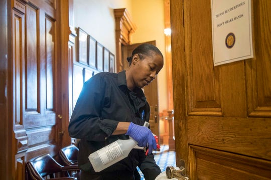 Custodian Brenda Love cleans the door handles at the Georgia State Capitol building during the 29th day of the Georgia Legislative session, Friday, March 13, 2020, in Atlanta.