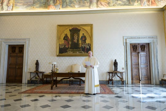 Pope Francis prays in his private library at the Vatican on March 25, 2020.