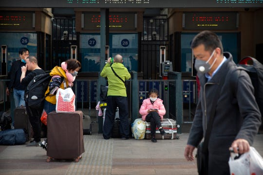 Travelers wearing face masks walk outside the Beijing Railway Station in Beijing, March 25, 2020. Some train stations and bus services reopened in China's Hubei Province on Wednesday and people who passed a health check would finally be allowed to travel for the first time since the coronavirus outbreak surged in January.