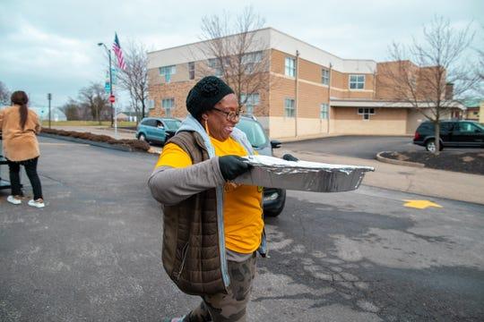 """Un voluntario lleva una bandeja de comida del restaurante ascendiente Akron a un automóvil que aplazamiento el martes en Akron, Ohio. La Fundación de la Grupo LeBron James proporcionó comidas a los estudiantes de su escuela y sus familias. """"Ufano ="""" 540 """"data-mycapture-src ="""" """"data-mycapture-sm-src ="""" """"/> <meta itemprop="""