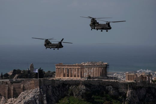 Greek military helicopters fly over the Acropolis on Greece's Independence Day, in Athens on Wednesday, March 25, 2020. The annual military parade commemorates Greek Independence Day, which marks the start of the war of independence in 1821 against the 400-year Ottoman rule, was cancelled on Wednesday amid a circulation ban imposed to slow the spread of the COVID-19 but a flyover with jets and helicopters took place.