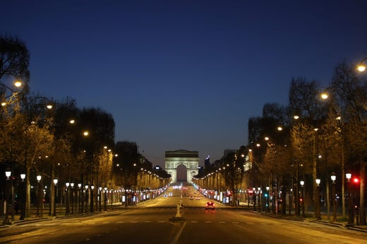 The empty Champs-Elysees Avenue and the Arc de Triomphe in Paris, at night on March 24, 2020, on the eighth day of a lockdown aimed at curbing the spread of the COVID-19 coronavirus in France.