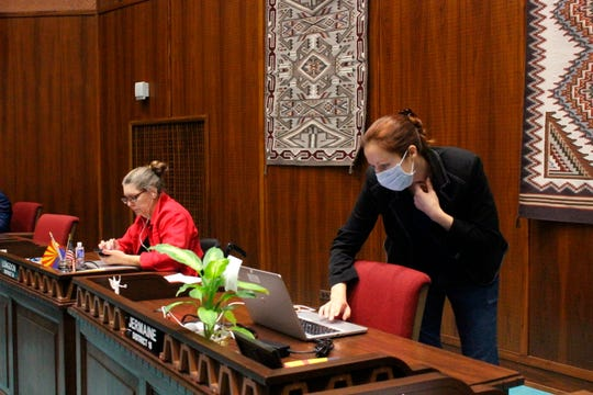 State Rep. Jennifer Jermaine, wearing a mask, looks at documents on her computer as fellow Democratic Rep. Jennifer Longdon, left, looks at her phone before the start of an unusual floor session at the Arizona House in Phoenix, on Thursday, March 19, 2020.