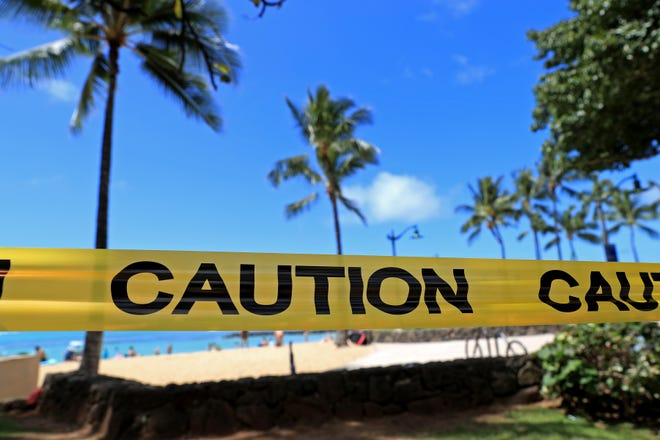 With beachgoers in the background, yellow caution tape is wrapped across an area of Waikiki, Friday, March 20, 2020, in Honolulu. Honolulu closed all public parks and recreation areas Friday until the end of April in an effort to help stop the spread of the coronavirus.