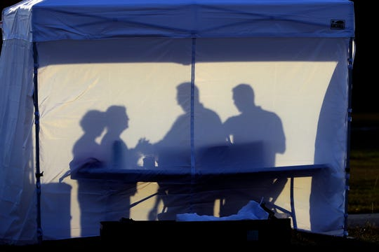 Medical personnel are silhouetted against the back of a tent before the start of coronavirus testing in the parking lot outside of Raymond James Stadium early March 25, 2020, in Tampa, Fla. The testing is being done by appointment only.