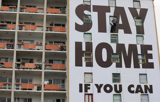 A billboard is installed on an apartment building in Cape Town, South Africa, March 25, 2020, before the country of 57 million people, will go into a nationwide lockdown for 21 days on Thursday to fight the spread of the new coronavirus.