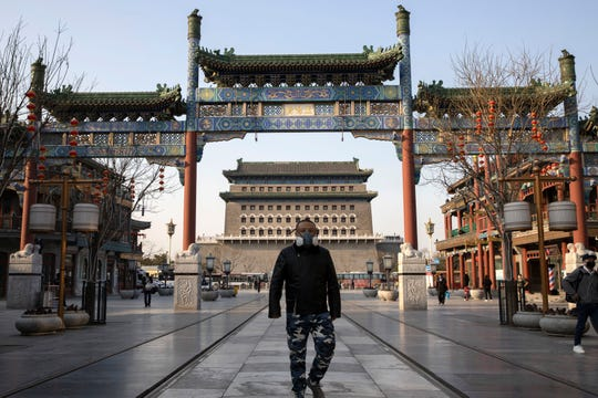 A man wearing a face mask walks through a quiet retail district in Beijing on Monday, March 23, 2020. Even while social distancing and quarantines for new arrivals remain the norm, China is striving to restore activity in the world's second-largest economy after the shutdown over the coronavirus outbreak. (AP Photo/Ng Han Guan) /// ORG XMIT: XHG109