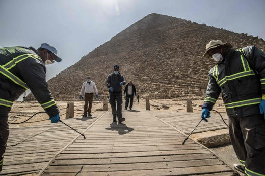 Egyptian municipality workers disinfect the Giza pyramids necropolis on the southwestern outskirts of the Egyptian capital Cairo on March 25, 2020 as protective a measure against the spread of the coronavirus COVID-19.