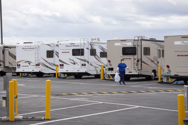 A worker walks by motor homes being prepared to house people under quarantine for the coronavirus. The RVs were brought to Dockweiler State Beach in Los Angeles to take care of people who can't be near others until it is determined if they have the virus.