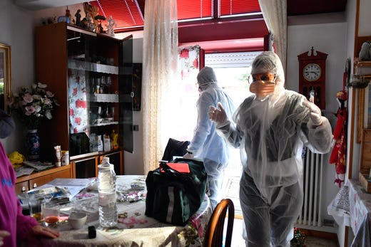 Medical staffers wearing protective gear, part of a special unit performing house calls, work in Bergamo, northern Italy, one of the areas worse-affected by coronavirus, March 25, 2020.