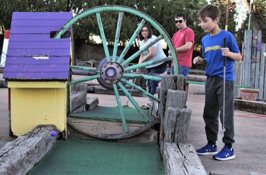 Eli Henry, right, watches Starla Henry's purple ball ricochet off the wheel Eli spun and bounce toward the hole at Play Faire Park, as Travis Henry, center, watches. The trio had the miniature golf course to themselves toward closing time Wednesday evening.