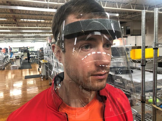 Kitsbow product engineer Peter Shoemaker of Asheville tests one of the first face shields that the Old Fort-based bicycle clothing manufacturer is now making. The company has switched from bike apparel to making PPE in light of the coronavirus pandemic.