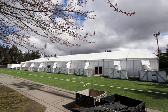 One of a pair of massive temporary buildings meant for use as a field hospital for coronavirus patients stands on a soccer field in the Seattle suburb of Shoreline. With U.S. hospital capacity stretched thin, hospitals around the country are scrambling to find space for a coming flood of COVID-19 patients, opening older closed hospitals and repurposing other buildings.
