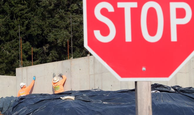 A construction crew works on a project at the intersection of Clear Creek Road and Pete Ross Way in Silverdale on Thursday, March 26, 2020.