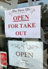 A COVID-19 sidewalk sign says The Dove III is open for takeout in downtown Melbourne.
