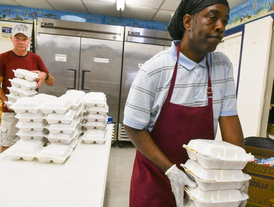 Staff member Woodrow Barfield and volunteer Wesley Smith, the former chef at Central Brevard Sharing Center in Cocoa, carry out boxed lunches to be distributed to the nonprofit's clients.