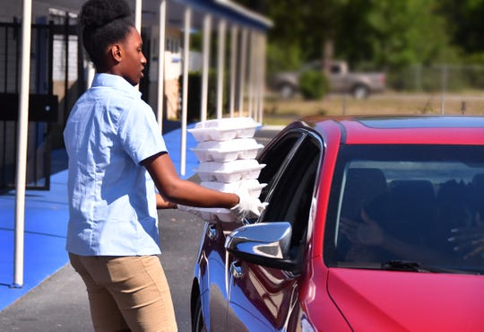 Zoniya Clark delivers lunches to a family at Emma Jewel Charter Academy in Cocoa. School officials are giving out free lunches during the school's closure, with many students showing up for meals. On Wednesday it was fresh fruit, a hot dog, beans and tater tots.