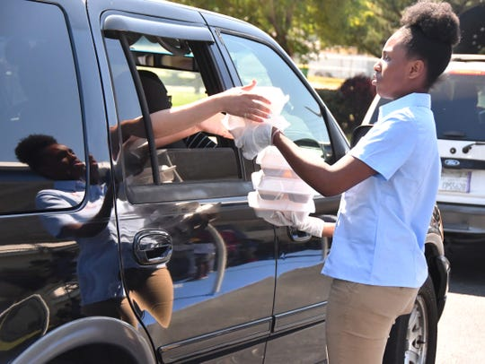 Zoniya Clark passes lunches to a family  at Emma Jewel Charter Academy in Cocoa. School officials are giving out free lunches during the school's closure, with many students showing up for meals. On Wednesday it was fresh fruit, a hot dog, beans and tater tots.