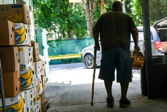 A client leaves after receiving a meal at the Central Brevard Sharing Center in Cocoa.