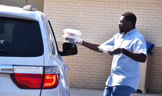 Alton Edmond hands lunches to a family at Emma Jewel Charter Academy in Cocoa. School officials are giving out free lunches during the week, with many students showing up for meals. On Wednesday it was fresh fruit, a hot dog, beans and tater tots.