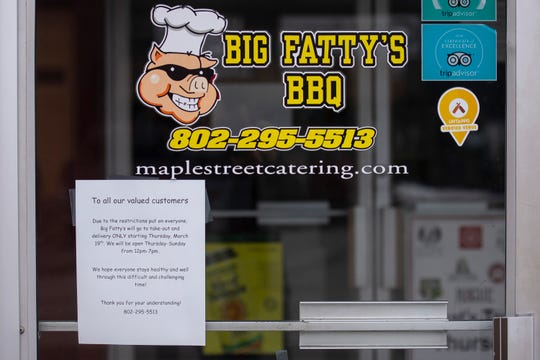 A sign on the door of Big Fatty's BBQ in White River Junction notifies customers of the recent mandates limiting dining options to takeout or delivery.