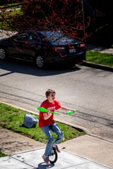 Joey Holt, 18, practices juggling while riding his unicycle around his street in Fort Thomas, Kentucky on Wednesday, March 25, 2020. Holt is a performer with Cincinnati Circus Company.