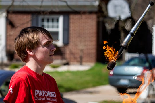 Joey Holt, 18, juggles fire batons for his neighbors in Fort Thomas, Kentucky on Wednesday, March 25, 2020.