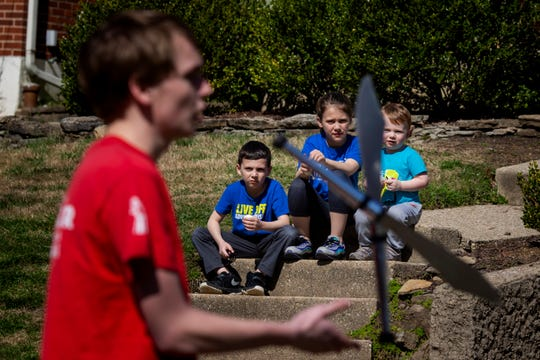 Henry Griffith, 7, Olivia Griffith, 9, and Ben Griffith, 3, watch Joey Holt, 18, juggling knives on their street in Fort Thomas, Kentucky on Wednesday, March 25, 2020.
