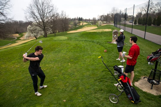 Mike Seliga, left, prepares to tee off while golfing with friends at Devou Park Golf Course in Covington, Ky., on Thursday, March 26, 2020.