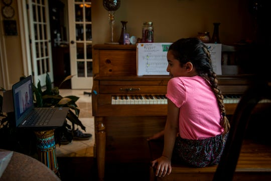 Sofia Eyada, 8, practices piano during her virtual lesson at her home in Mason on Friday, March 20, 2020.