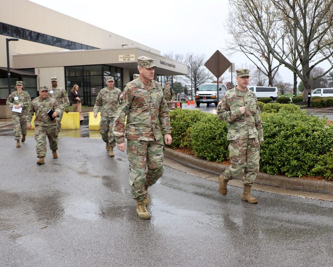 BACH Commander Col. Patrick T. Birchfield (right) leads 101st Airborne Division (Air Assault) and Fort Campbell Commanding General, Maj. Gen. Brian Winski (left) to a drive-up clinic established outside the hospital where medical staff are seeing patients referred for possible COVID-19  related symptoms.
