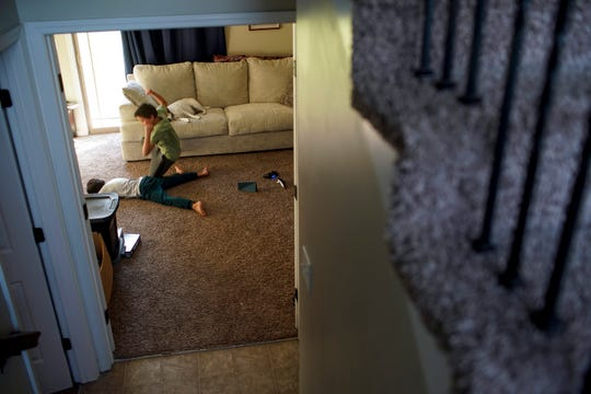 Hayden Walton, 9, jumps off the couch to do a wrestling elbow slam onto the floor near his brother, Donovan Walton, 7, while the kids are out of school at the Walton household in Clarksville, Tenn., on Wednesday, March 25, 2020.